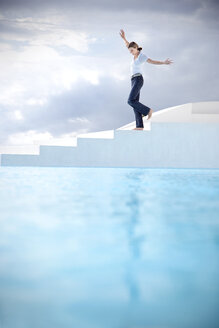 Spain, Mallorca, woman balancing on stairs with beside a swimming pool - TOYF001188