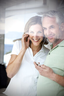 Portrait of smiling couple with earphones and mp3 player looking through window - TOYF001208