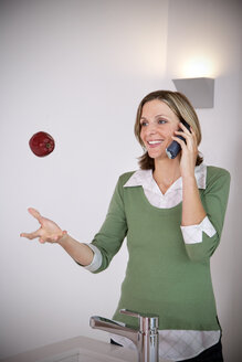 Portrait of smiling woman playing with an apple while telephoning in the kitchen - TOYF001212