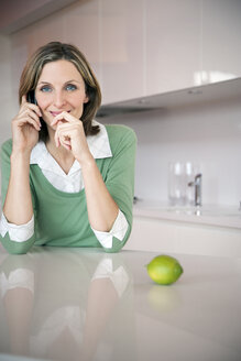 Portrait of smiling woman telephoning in the kitchen - TOYF001215