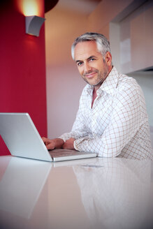 Portrait of smiling man with laptop - TOYF001402