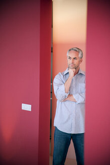 Portrait of pensive man standing between two red walls - TOYF001233