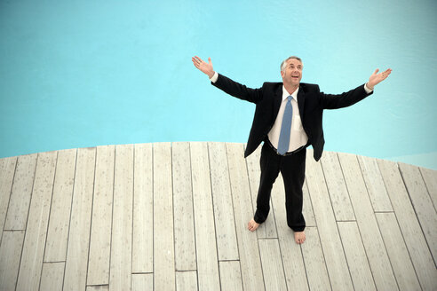 Barefoot businessman wearing black suit standing in front of swimming pool with arms raised - TOYF001228