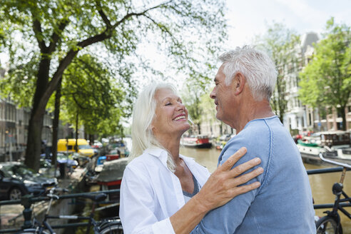 Netherlands, Amsterdam, happy senior couple embracing at town canal - FMKF002010