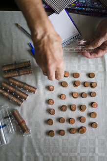 Elderly woman counting money, making stacks of Euro cents - RAEF000415