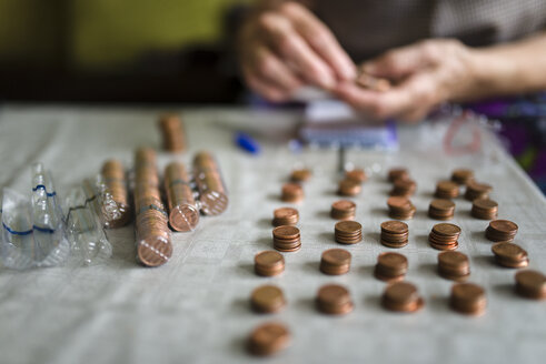Elderly woman counting money, making stacks of Euro cents - RAEF000413