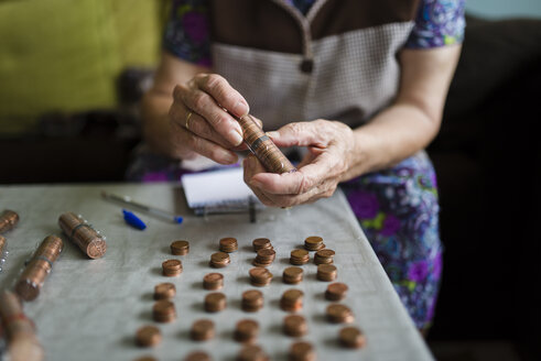 Elderly woman counting money, making stacks of Euro cents - RAEF000411