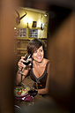 Smiling woman holding red wine glass in a traditional Spanish bar - JASF000031