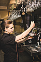 Waitress tapping beer in pub - JASF000033