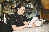 Waitress in bar with digital tablet looking at orders - JASF000035