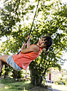 Portrait of little girl swinging in the garden - MGOF000581
