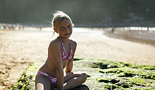 Portrait of a blond little girl sitting on a rock on the beach - MGOF000587