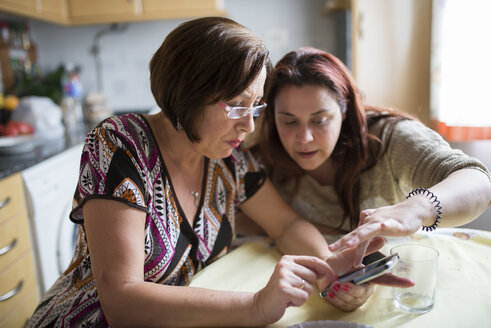 Woman helping senior woman how to use a smartphone - RAEF000420
