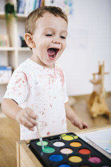 Portrait of laughing little boy painting with watercolours - JRFF000025