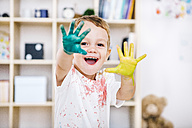 Portrait of smiling little boy showing his painted hands - JRFF000023