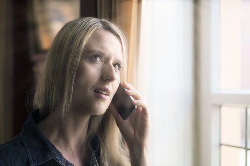 Portrait of blond woman telephoning with smartphone - FRF000327
