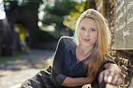 Portrait of blond woman sitting on a bench - FRF000324
