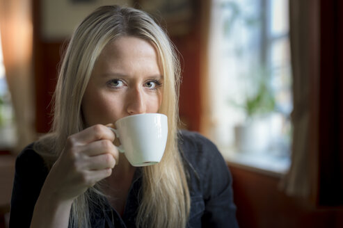 Portrait of blond woman drinking cup of coffee - FRF000317