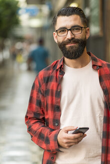 Portrait of smiling hipster with smartphone - JASF000087