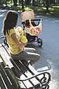 Mother with baby on park bench - DEGF000516