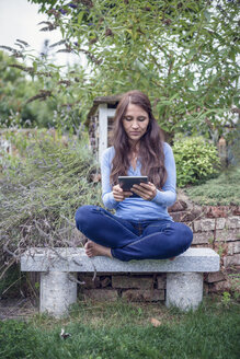 Woman sitting cross-legged on a bench in the garden looking at digital tablet - OPF000077