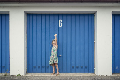 6 year old girl in front of garage door with number 6 - OPF000080