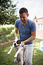 Man carrying a French bulldog in a garden - RAEF000431