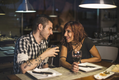 Happy couple in restaurant having dinner and drinking wine - JASF000064