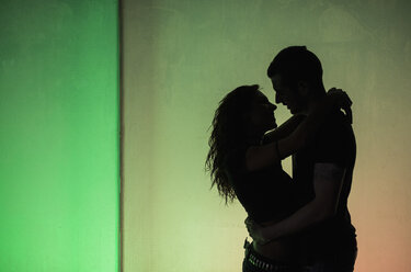 Silhouettes of young couple in love on a wall at greenish light - JASF000071