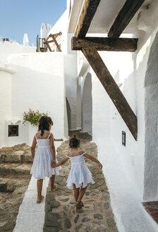 Spain, Balearic Islands, Menorca, Binibeca, back view of two little sisters walking hand in hand - MGOF000654