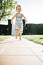Little boy running barefoot on floor plates in the garden - JRFF000038