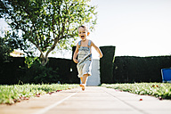Excited little boy running barefoot on floor plates in the garden - JRFF000041