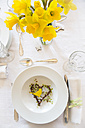 Place setting on laid table with daffodils at springtime - LVF003770