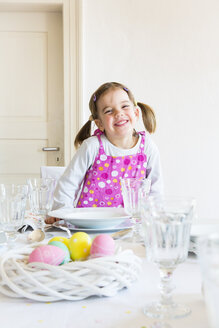 Portrait of smiling little girl sitting at laid table - LVF003778