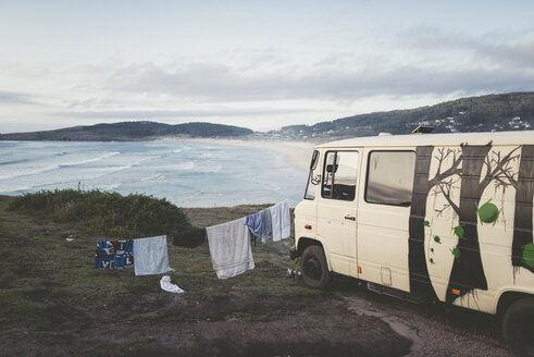 Spain, Ferrol, camper van with clothes hanging on a rope with view to Punta Penencia beach - RAE000486
