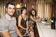 Portrait of three smiling friends in a restaurant - JASF000090