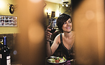 Smiling woman holding red wine glass in a traditional Spanish bar - JASF000094