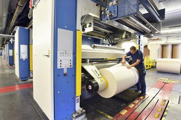 Man working at printing machine in a printing shop - LYF000469
