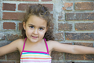 Portrait of little girl leaning against brick wall - ERLF000029