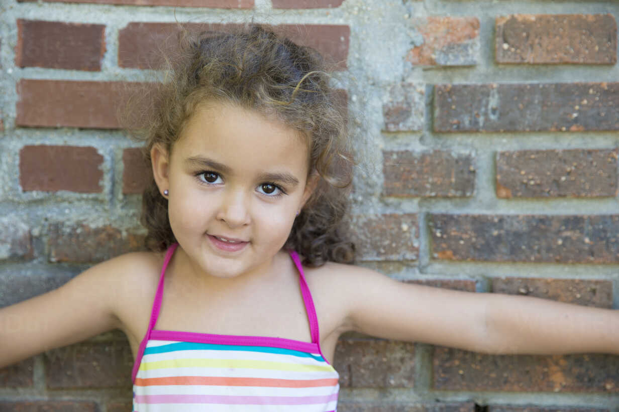Portrait of little girl leaning against brick wall - ERLF000029 - Enrique Ramoz/Westend61