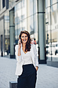 Happy businesswoman outdoors on cell phone - CHAF001415