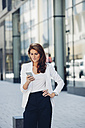 Businesswoman outdoors looking on cell phone - CHAF001416