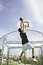 Young man playing basketball, dunking ball - ABZF000117