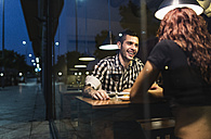 Couple in restaurant having dinner and drinking wine behind the window pane - JASF000079