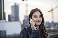 Germany, Frankfurt, portrait of smiling woman telephoning with smartphone - RIBF000248