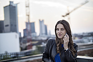 Germany, Frankfurt, portrait of young woman telephoning with smartphone - RIBF000249