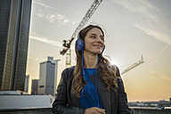 Germany, Frankfurt, smiling woman hearing music with headphones - RIBF000254
