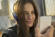 Germany, Frankfurt, portrait of smiling woman hearing music with headphones looking at smartphone - RIBF000257