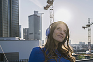 Germany, Frankfurt, portrait of smiling woman hearing music with headphones at backlight - RIBF000261