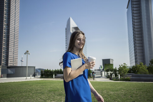 Germany, Frankfurt, smiling woman with coffee to go and mini tablet - RIBF000274
